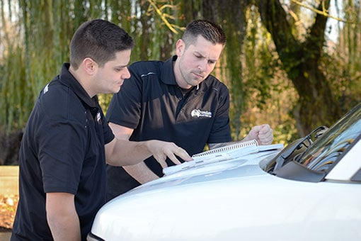 Premium Electric owners Mike and Tristan studying a manual on the hood of their van